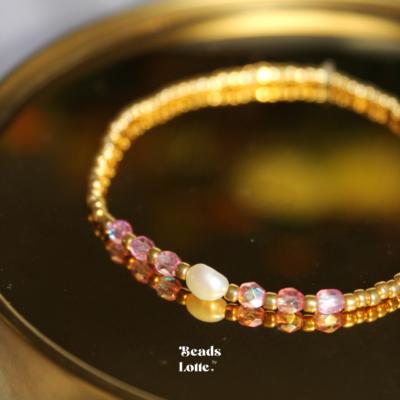 Goud armbandje met parels en roze kraaltjes
