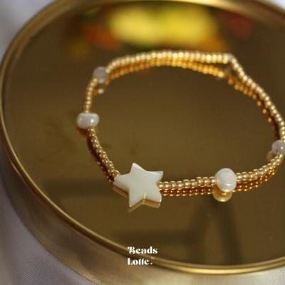 Gouden armbandje met parels en schelp ster