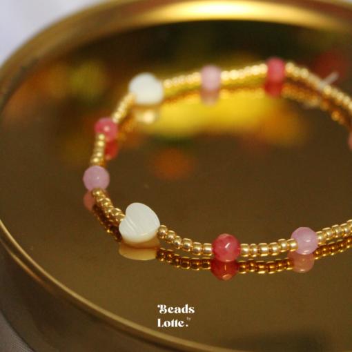 Goud armbandje met roze kraaltjes en hartjes schelp