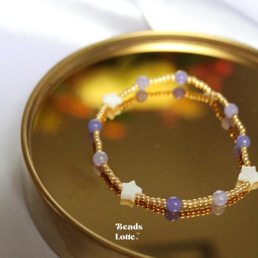 Goud armbandje met paarse kraaltjes en sterren schelpen