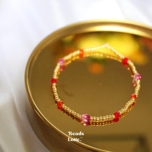 Goud armbandje met roze en rode tussenkraaltjes