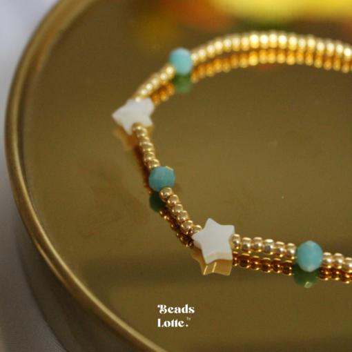 Goud armbandje met groene kraaltjes en schelpen sterretjes